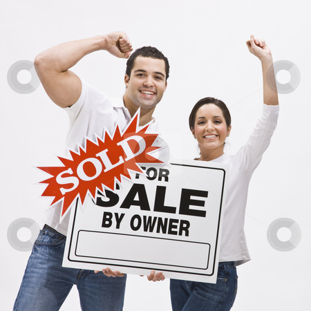 Couple with FSBO home sold sign. stock photo, Happy Couple with sold sign for home pumping their fists in the air in celebration. Square composition. by Jonathan Ross