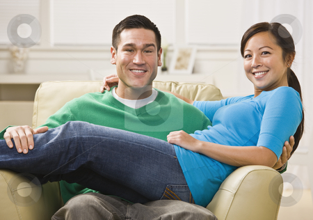 Attractive Smiling Couple on Sofa stock photo, Attractive Asian Couple relaxing together on their living room couch. Horizontally framed photo. by Jonathan Ross