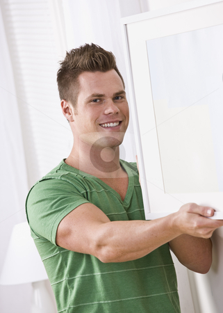 Man Hanging a Picture Frame stock photo, A man holding a picture frame.  He is smiling at the camera and the background is white. Vertically framed shot. by Jonathan Ross