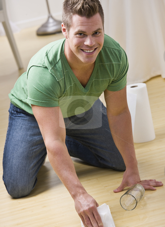 Man Cleaning Spill stock photo, An attractive young man cleaning up spilt water on the floor.  He is smiling at the camera. Vertically framed shot. by Jonathan Ross