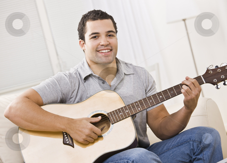 Attractive Man with Guitar stock photo, An attractive young man playing the guitar.  He is seated on a couch and is smiling at the camera.  Horizontally framed shot. by Jonathan Ross