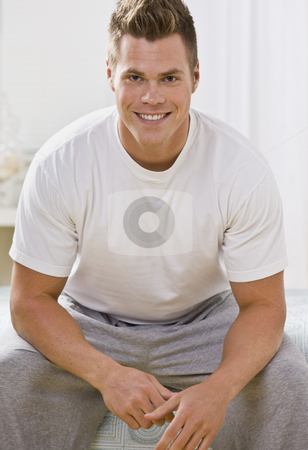 Attractive Caucasian Man Smiling at the Camera stock photo, An attractive young man sitting down and smiling directly at the camera. Vertically framed photo. by Jonathan Ross