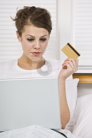 Attractive Woman with Credit Card and Laptop stock photo, An attractive young woman holding a credit card and peering at a laptop screen.  She is sitting in bed and has a contemplative expression. Vertically framed shot. by Jonathan Ross