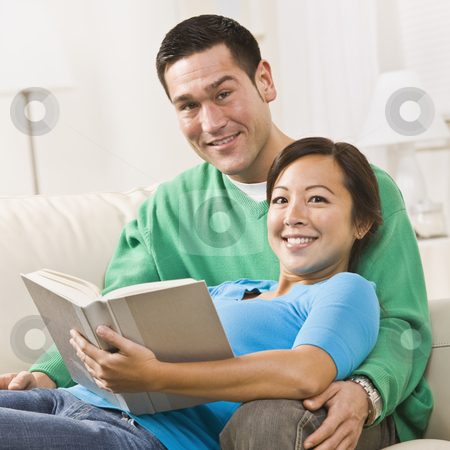 Couple Reading stock photo, An attractive young couple sitting on a couch together with a book.  The female is sitting in the male's lap.  They are smiling directly at the camera. Square framed shot. by Jonathan Ross