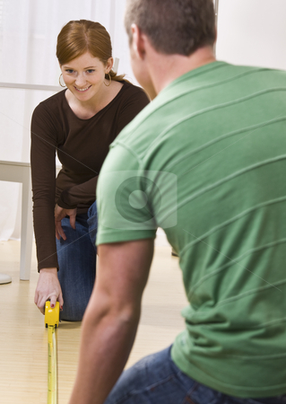 Couple measuring floor of their apartment. stock photo, Attractive couple measuring floor with tape measure. vertical by Jonathan Ross