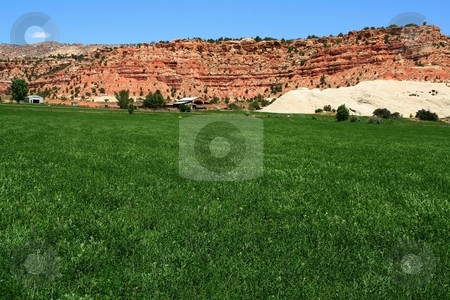 Desert Farm 4 stock photo, View of a farm in the  desert with hay in the foreground and a red rock mountain  in the background with blue sky by Mark Smith
