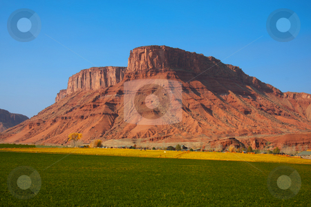 Red Rock Farm stock photo, View of a farm in the  desert with hay in the foreground and a red rock mountain  in the background with blue sky by Mark Smith