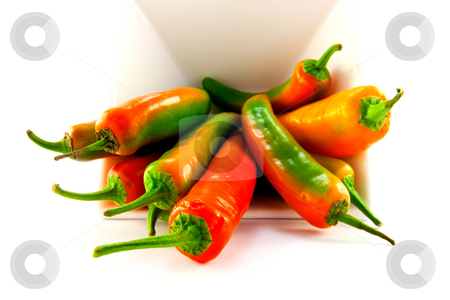 White Bowl of Chillis stock photo, Red and green chillis spilling out of a white square bowl with clipping path on a white background by Keith Wilson