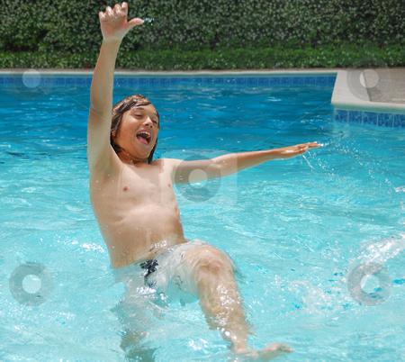 Summer Fun in Swimming Pool stock photo, Teen boy having fun in swimming pool with white flower bush background. by Denis Radovanovic