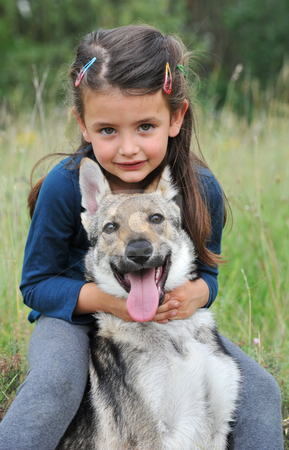 Little girl and her baby wolf dog stock photo, Little girl and her baby purebred wolf dog by Bonzami Emmanuelle