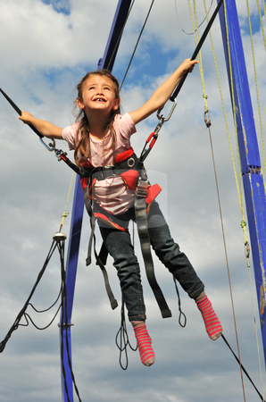 Bungee jumping stock photo, Little girl jumping on the trampoline (bungee jumping). by Bonzami Emmanuelle