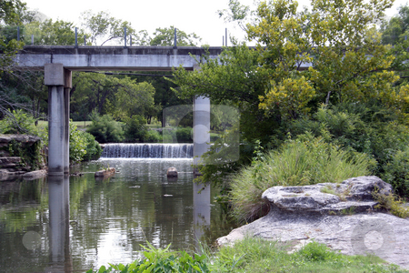 Calm Creek stock photo, A calm creek with a train bridge and a waterfall in the background by Brandon Seidel