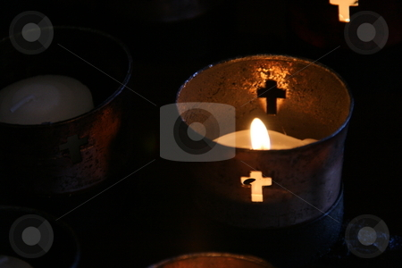 Candles burning in religious cups stock photo, Small votive candles burning in religious cups with cross cutouts by Brandon Seidel