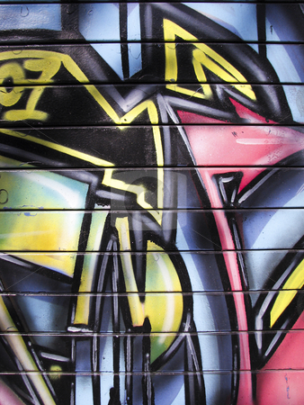 Graffiti painted garage door stock photo, Bright yellow and blue metal garage door by Annette Davis