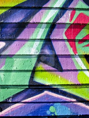 Vibrant graffiti on wood slatted wall stock photo, Purple, pink and green graffiti on an abandoned wood wall by Annette Davis