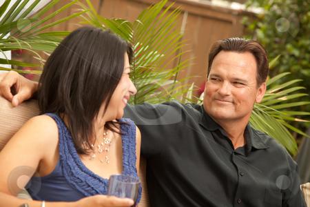 Attractive Hispanic and Caucasian Couple Drinking Wine stock photo, Attractive Hispanic and Caucasian Couple Drinking Wine Outside. by Andy Dean