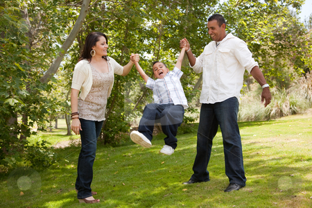Young Family Having Fun in the Park stock photo, Hispanic Man, Woman and Child having fun in the park. by Andy Dean