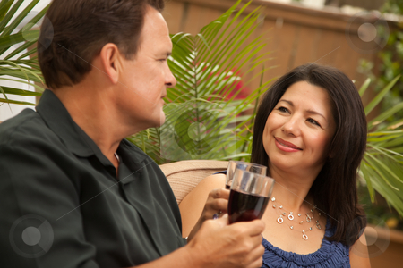 Attractive Hispanic and Caucasian Couple Drinking Wine stock photo, Attractive Hispanic and Caucasian Couple Drinking Wine Outside. by Andy Dean