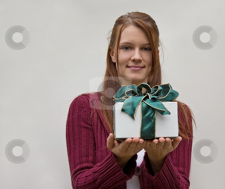 Young Woman Giving Gift stock photo, This brunette young pretty woman is giving a gift in a white box wrapped with a green bow. by Valerie Garner