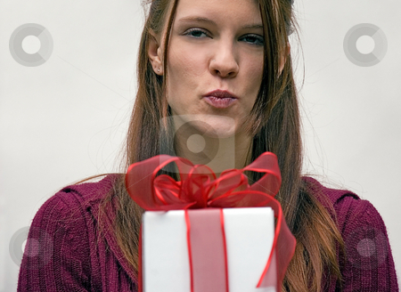 Woman Puckering Lips with Gift stock photo, This young woman is pucking up to give a kiss to the person she is giving this red bow wrapped gift to. by Valerie Garner