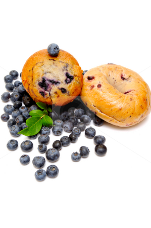 Blueberry Muffin And Bagel stock photo, Fresh blueberries surround a single blueberry muffin and a bagel on a light background by Lynn Bendickson