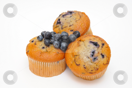 Blueberries And Muffin stock photo, Blueberry muffins with fresh blueberries on top of the cakes on a light colored background. by Lynn Bendickson