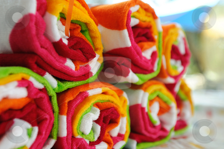 Rolled Up Beach Towels stock photo, Multi-colored beach towels rolled up ready to use at the pool or beach. by Lynn Bendickson