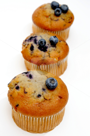 Muffins With Blueberries stock photo, Three blueberry muffins with fresh berries on top on a light colored background by Lynn Bendickson