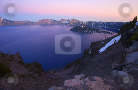 Crater Lake Sunset stock photo, Crater Lake at sunset. Mt. McLoughlin at 9945 feet hides on the horizon. The deepest lake in the United States formed by in the caldera of Mt. Mazama a volcano that blew its top many, many years ago. by Mike Dawson