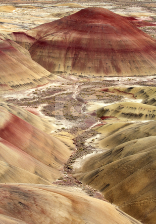 Painted Hills stock photo, Oregon's Painted Hills living up to their colorful name, as iron and other minerals stain the clay covered hills. by Mike Dawson