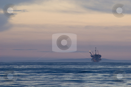 Offshore oil rig stock photo, Off shore oil drilling rig at sunset by Stephen Gibson