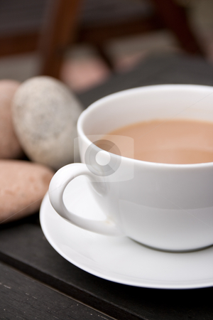 Cup of Tea stock photo, Outdoor cup of tea in a white cup and saucer with stones on a wooden background by Keith Wilson