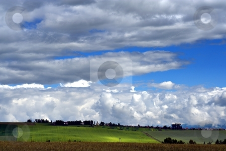 Summer in country stock photo, A village on horizon in summer day with fields and cloudy sky by Juraj Kovacik