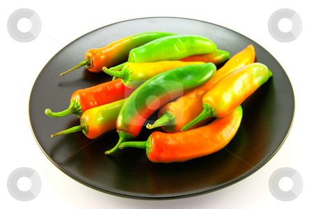 Assorted Chillis on a Black Plate stock photo, Red, green and yellow whole chillis on a black plate with clipping path on a white background by Keith Wilson
