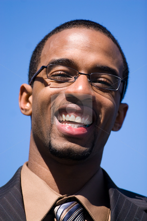 Happy Business Man stock photo, African American man wearing glasses and a business suit isolated over a blue sky background. by Todd Arena