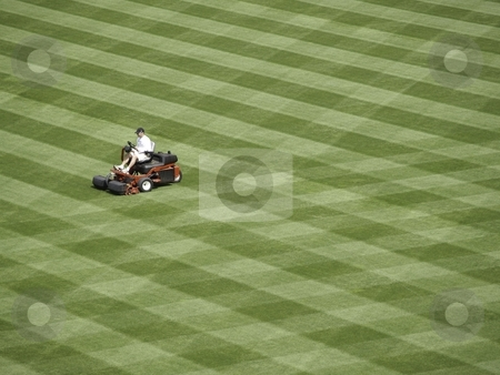 A lot to mow stock photo, A solitary man (unidentifiable) mows a huge field into stripes by Cora Reed
