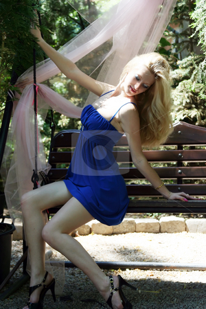 Girl on seesaw stock photo, The young girl sits on the seesaw by Aleksandr GAvrilov