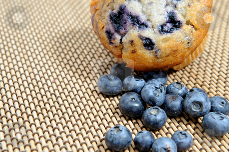 Blueberries And Muffin stock photo, Fresh picked blueberries next to a berry muffin on a woven wood place mat by Lynn Bendickson