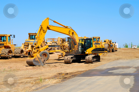 Excavator And Heavy Equipment stock photo, Heavy construction equipment sits idle lined up along a new asphalt road by Lynn Bendickson
