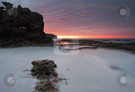 Window on Dawn stock photo, A window on a glorious sunrise in a large limestone boulder on the beach at Pennington Bay South Australia by Mike Dawson