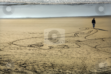 Woman Sand Painting Beach Walking to Water San Francisco Califor stock photo, Woman Sand Painting Drawing Walking on the Beach Towards Water Point Lobos San Francisco California by William Perry
