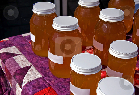 Many Jars of Honey on Quilt stock photo, Table of many jars of fresh honey displayed on a homemade quilt. by Valerie Garner