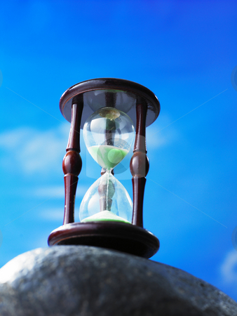 Hourglass stock photo, Hour glass on the rock with blue sky as back ground by eskaylim
