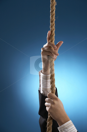 businessman with suit pulling rope stock photo, A businessman with suit pulling rope upward by eskaylim