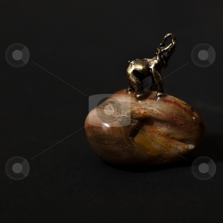 Elephant stock photo, Small metal statue of elephant on a stone. by Mariusz Jurgielewicz