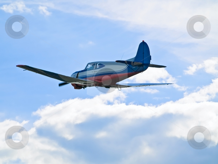 Aeroplane  stock photo, Single aeroplane flying in blue sky  through the clouds by Sergej Razvodovskij