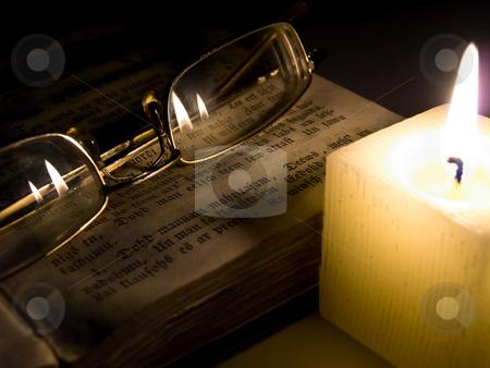 Glasses  stock photo, Glasses at the book near candle in the night by Sergej Razvodovskij