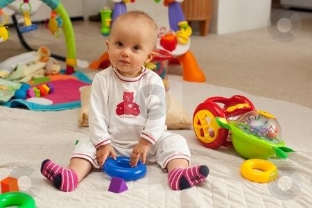 Playmat stock photo, Caucasian baby girl playing on a floor. by Mariusz Jurgielewicz