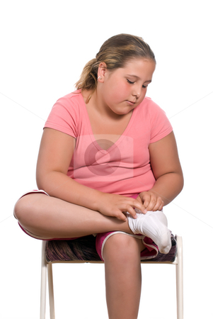 Putting On Socks stock photo, A young preteen girl is sitting on a stool and putting on her socks, isolated against a white background by Richard Nelson