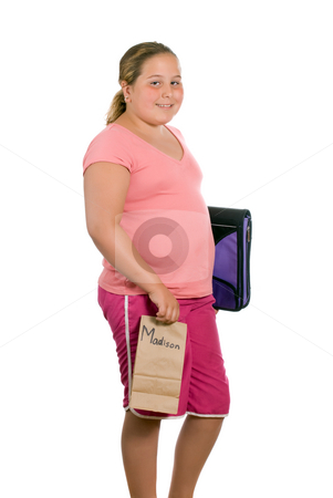 School Girl stock photo, A preteen is holding her school binder and a brown paper lunch bag and is off to school, isolated against a white background - artificial name on the lunchbag by Richard Nelson